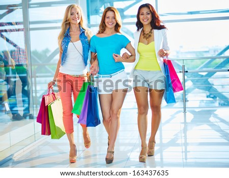 Portrait of happy girlfriends with paperbags walking down trade center after shopping - stock photo