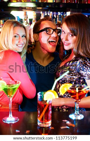 Portrait of happy girls and funny barman looking at camera at party - stock photo