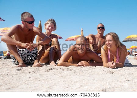 Portrait of happy girls and guys lying on sand on summer vacation - stock photo