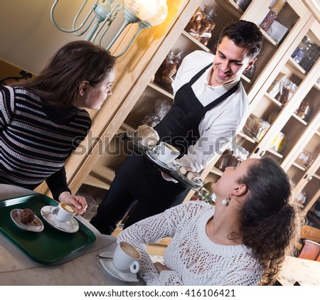 Portrait of happy girls chatting in coffee-house and cheerful smiling waiter