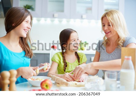 Portrait of happy girls helping their mother to cook pastry - stock photo