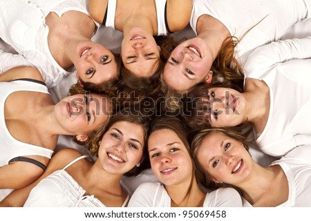 portrait of happy girls lying in a circle at the floor in white