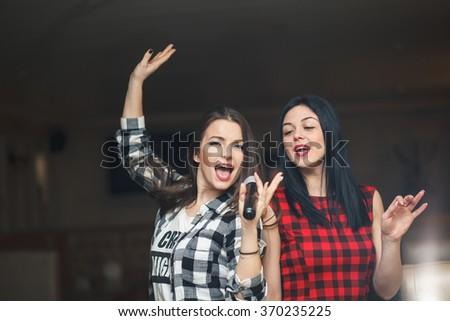 Portrait of happy girls singing in microphone in the karaoke bar - stock photo