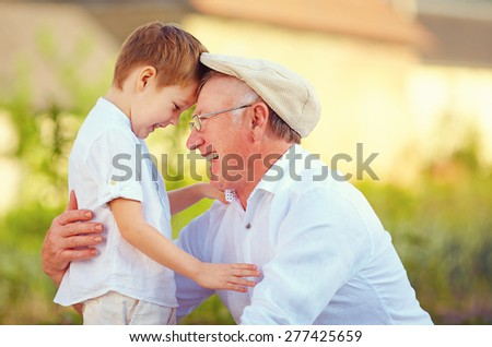 portrait of happy grandfather and grandson bow their heads - stock photo