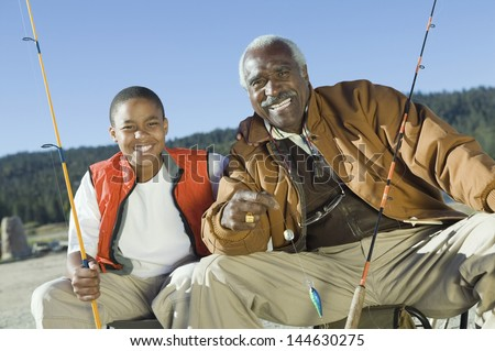 Portrait of happy grandfather and grandson fishing together - stock photo