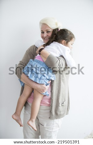 Portrait of happy grandmother carrying granddaughter at home - stock photo