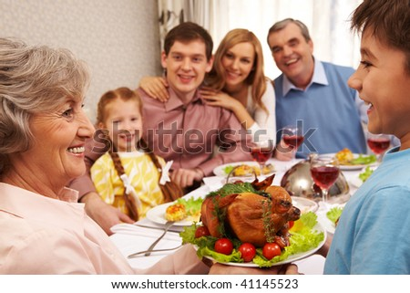 Portrait of happy grandmother holding tray with roasted turkey and looking at her grandson - stock photo