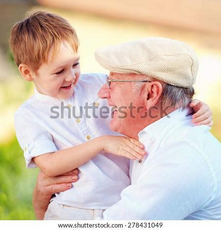 portrait of happy grandpa and grandson having fun outdoors - stock photo