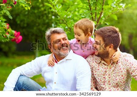 portrait of happy grandpa, father and son in spring garden - stock photo