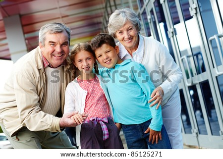 Portrait of happy grandparents and grandchildren by the mall - stock photo