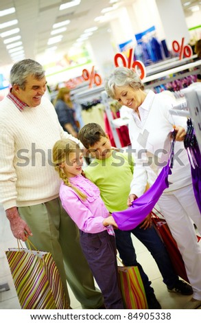 Portrait of happy grandparents and grandchildren choosing clothes in the mall - stock photo