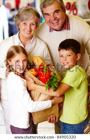 Portrait of happy grandparents and grandchildren holding package with food - stock photo