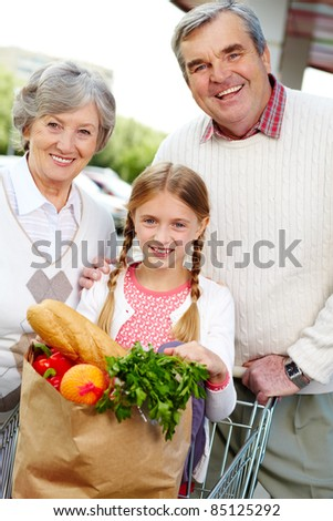 Portrait of happy grandparents and granddaughter after shopping