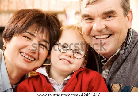 Portrait of happy grandparents and their grandson smiling at camera - stock photo