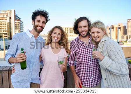Portrait of happy group of friends having fun with drink on outdoor rooftop terrace - stock photo