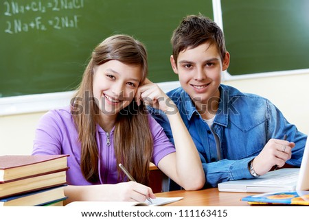 Portrait of happy guy and girl looking at camera - stock photo