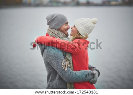 Portrait of happy guy and his girlfriend in embrace - stock photo