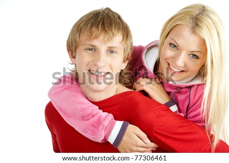 Portrait of happy guy being hugged by his pretty girlfriend