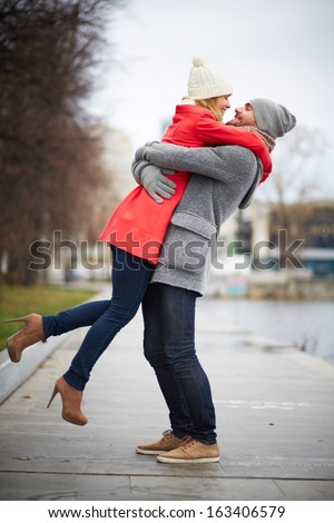 Portrait of happy guy holding his girlfriend in park - stock photo