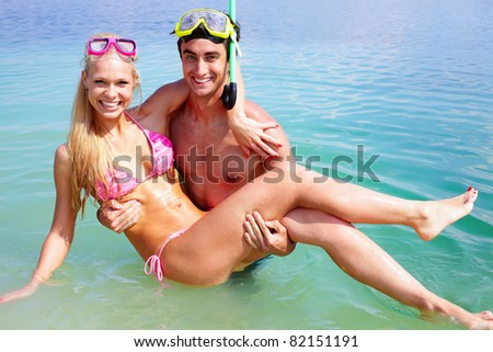 Portrait of happy guy holding his girlfriend while standing in water - stock photo