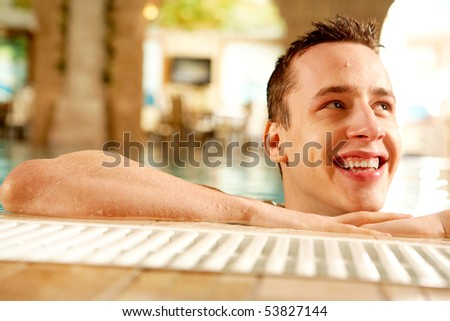 Portrait of happy guy laughing in swimming pool - stock photo