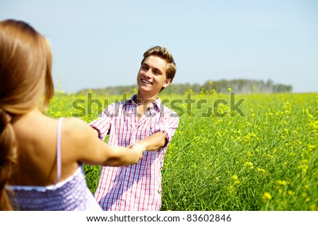Portrait of happy guy looking at his girlfriend in flower field - stock photo