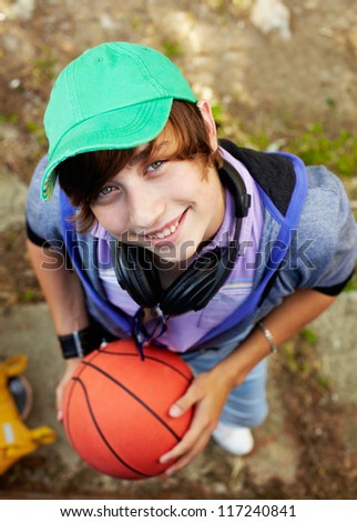 Portrait of happy guy with ball looking at camera in the park