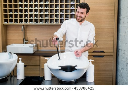 Portrait of happy hairstylist with water tap near sink at salon barbershop - stock photo