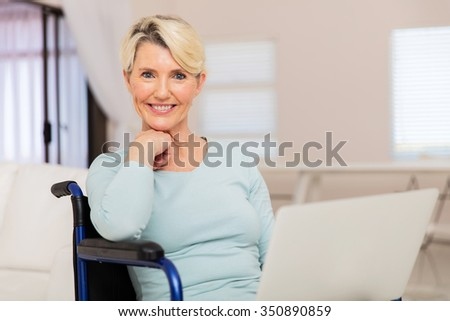 portrait of happy handicapped senior woman at home using laptop - stock photo