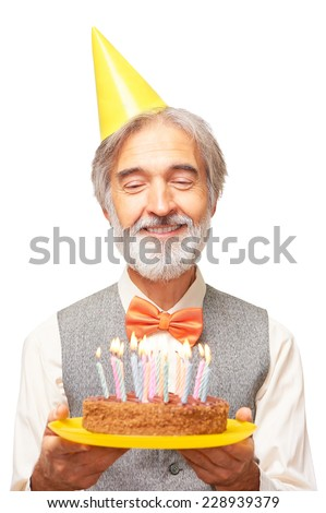 Portrait of happy handsome caucasian senior man with a gray beard and orange bowtie in yellow festive hood looking on birthday cake with candles in his hands isolated on white background - stock photo