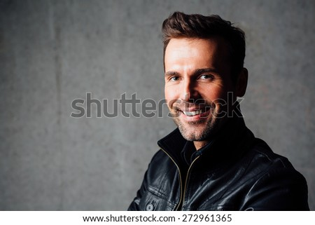 Portrait of happy handsome man in leather jacket