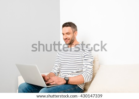 Portrait of happy handsome man sitting on couch and typing on laptop