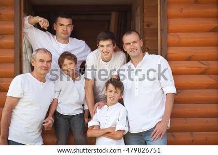 Portrait of happy handsome men on background of wooden house, three generations, grandfather, father, son, grandson., outdoor