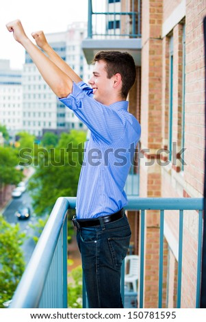 Portrait of happy, handsome, successful guy raising hands, arms outstretched in celebration and success, enjoying life on outside balcony, isolated on city background with trees and buildings