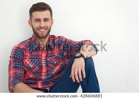 Portrait of happy handsome young man in casual wear sitting against white wall. - stock photo