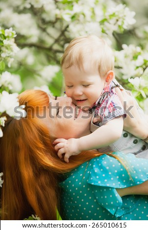 Portrait of happy happy mother ands son in spring garden. They playing and laughing. Blooming apple-trees. Family concept. Mothers day - stock photo