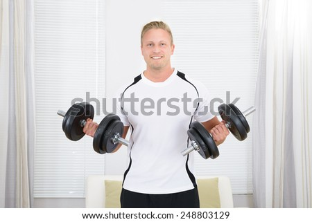Portrait Of Happy Healthy Man Lifting Weights - stock photo