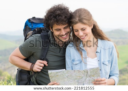 Portrait Of Happy Hikers Analyze The Map In Footpath - stock photo