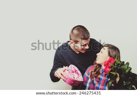 Portrait of happy hipster couple holding red paper hearts by their eyes - stock photo