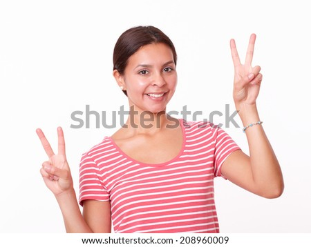 Portrait of happy hispanic lady with victory sign smiling at you on isolated studio
