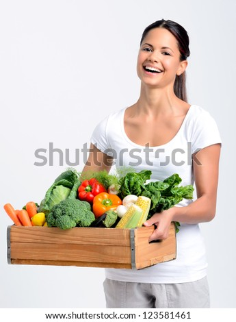 Portrait of happy hispanic woman holding a crate full of fresh organic vegetables on grey background, promoting healthy diet and lifestyle - stock photo