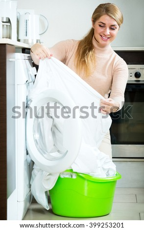 Portrait of happy housewife satisfied with quality of washing