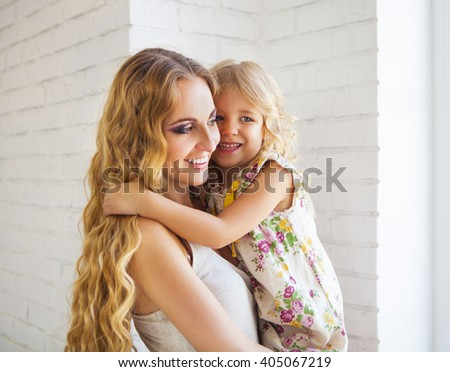 Portrait of happy hugging mother and daughter - stock photo