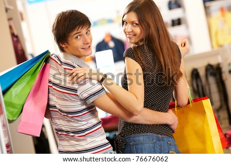 Portrait of happy husband and wife looking at camera during shopping