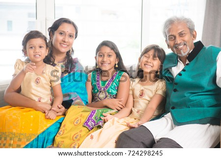 Portrait of happy Indian family at home, smile at camera. Asian parents and children indoors lifestyle.
