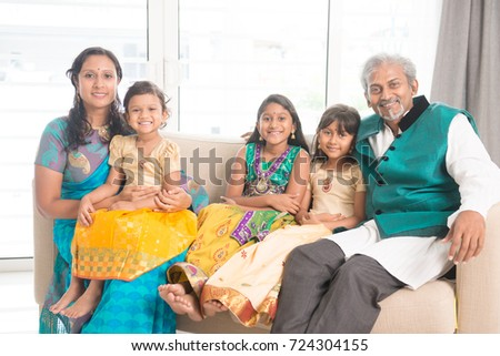 Portrait of happy Indian family in traditional clothes at home, smile at camera.