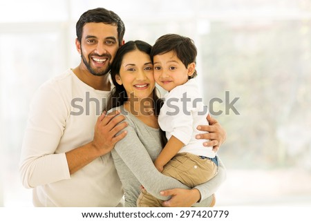 portrait of happy indian family of three standing indoors - stock photo
