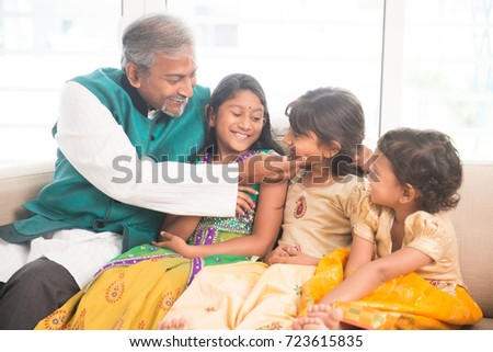 Portrait of happy Indian family sitting at home. Asian father and children indoors lifestyle.