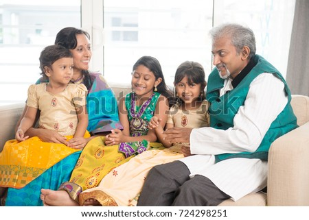 Portrait of happy Indian family talking at home. Asian people indoors lifestyle.