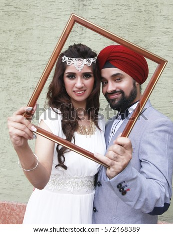 Portrait Of Happy Indian Wedding Couple Holding Frame Together